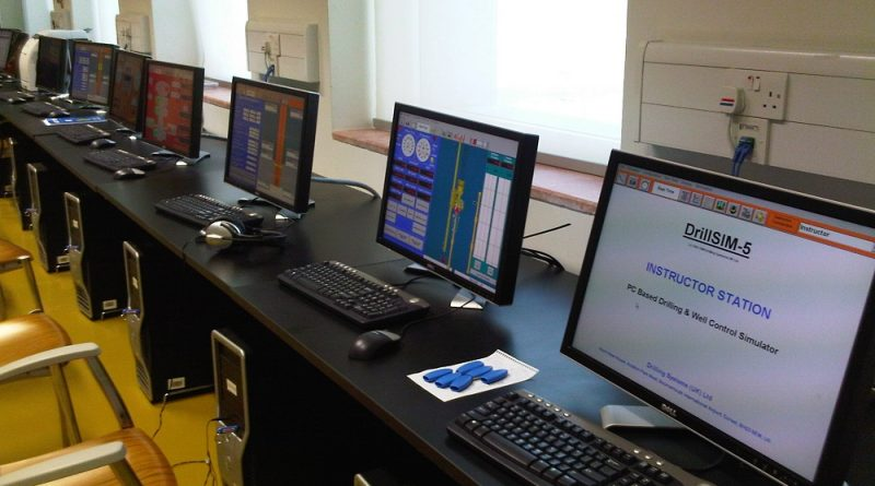 DrillSIM 5 drilling and well control simulation software on five computer screens in a classroom environment